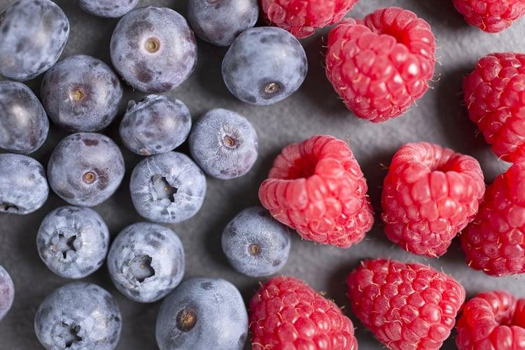 Fresh ripe summer raspberries and blueberries on black slate