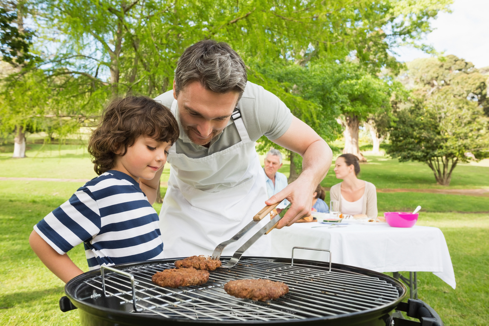 Man and son barbecuing with family in the background at park