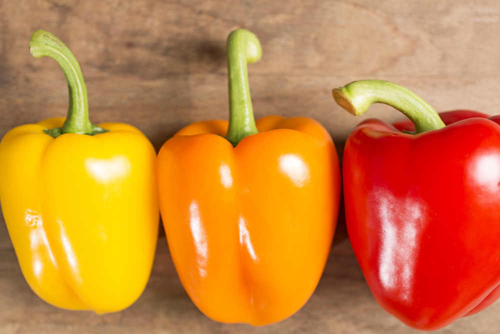 Selection of fresh red yellow and orange peppers on a wooden kitchen work surface